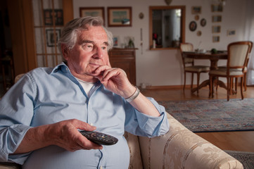 Frustrated senior watching television