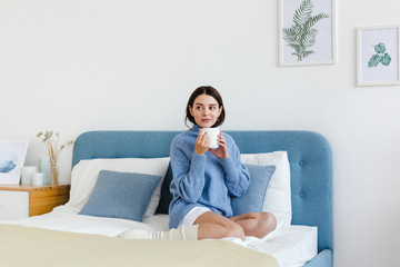 Girl in a blue sweater in interior Hygge style with a cup in hand sits on the bed