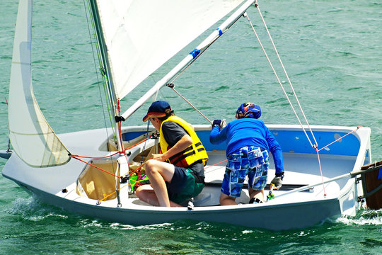 Two Boys Sailing in a small boat on salt water.