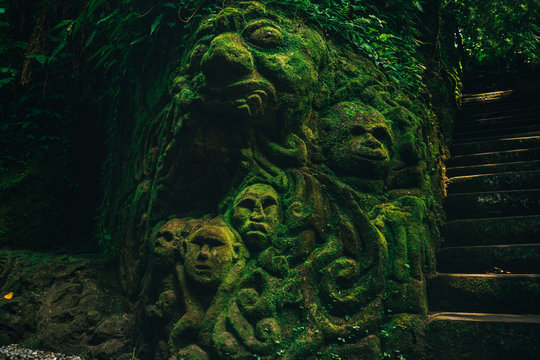 Carving demons faces on wall background covered with moss texture in Bali