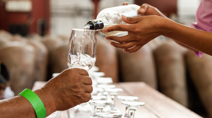 Hands pour wine in a glass