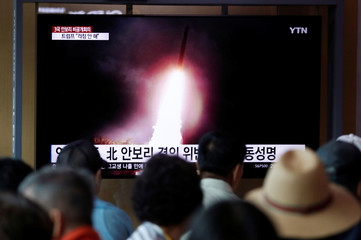 People watch a TV showing a file picture of a North Korean missile for a news report on North Korea firing short-range ballistic missiles, in Seoul