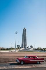Foto op Plexiglas Cubaanse oldtimers Revolution monument in La Havana Cuba with a red car