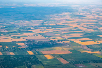 Aerial view of agricultural land patchwork crops in hazy atmosphere