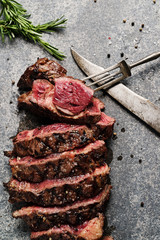 Prime Rib Steak on natural stone slab with old knife and fork
