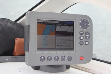 Close-up grey modern chartplotter device ob Motor boat dashboard, inscription on screen in Russian: local time, depth, map, trip, find, view