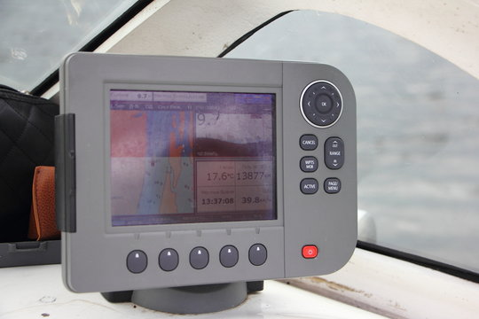 White motor boat dashboard in cockpit on glass background, close up gray chartplotter, inscription on screen in Russian: local time, depth, map, trip, find, view