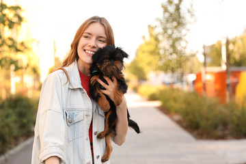 Young woman with adorable Brussels Griffon dog in park. Space for text