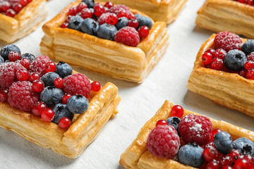 Fototapeten Brot Fresh delicious puff pastry with sweet berries on light table, closeup