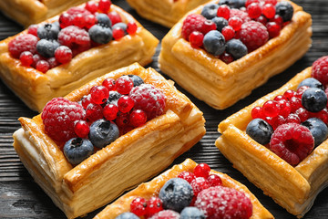 Fototapeten Brot Fresh delicious puff pastry with sweet berries on dark wooden table, closeup