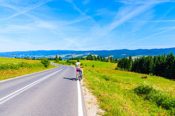 Young woman cyclist stopping on road and looking at Czorsztynskie lake on beautiful summer day, Pieniny Mountains, Poland