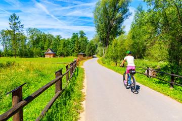 Young woman riding bike on cycling way along green fields near Czorsztynskie lake and Nowy Targ, Tatra Mountains, Poland