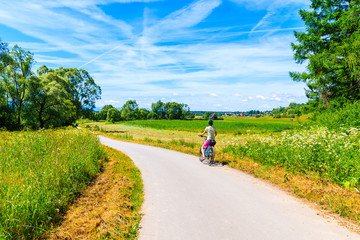 Young woman cyclist standing on cycling way along Dunajec river and looking at green farming fields near Czorsztynskie lake, Pieniny Mountains, Poland