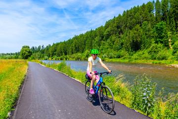 Obraz Young woman riding bike on cycling way along Dunajec river near Nowy Targ, Tatra Mountains, Poland - fototapety do salonu