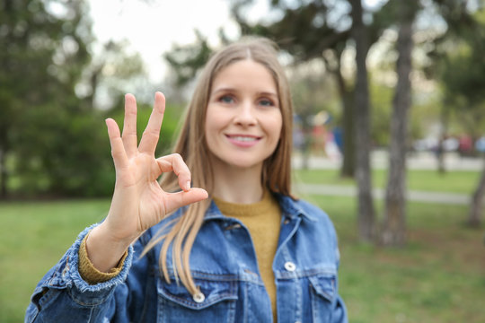 Young deaf mute woman using sign language outdoors