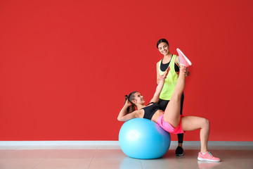 Young sporty woman with fitball doing exercises under supervision of her personal trainer near color wall