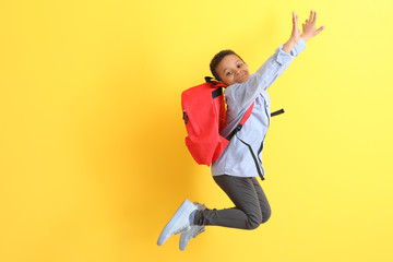Jumping African-American schoolboy on color background
