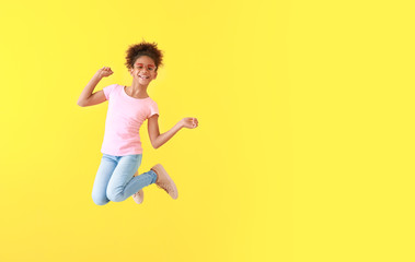 Jumping African-American girl in jeans on color background Fotoväggar