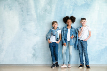 Stylish children in jeans clothes near color wall Wall mural