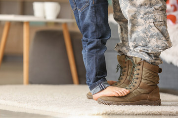 Child standing of feet of his military father at home