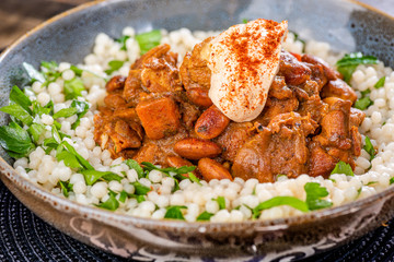 A traditional Moroccan dish called chicken Tajine featuring Saffron, Honey, Almonds, Dates, Couscous and Labneh