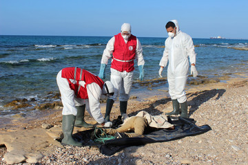 Libyan Red Crescent workers put the body of a migrant, who died after their wooden boat capsized, in a bag, in Khoms