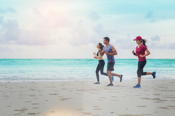 Peoples runner jogging at the beach with sunset background.