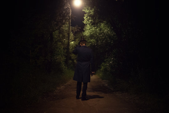 Detective agent in a leather hat and coat is walking through the night park with a handgun in a hand.