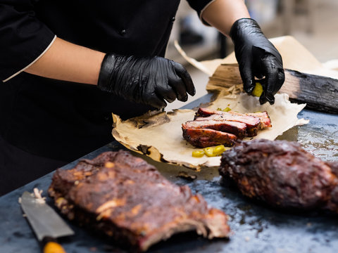 Grill restaurant kitchen. Cropped shot of chef in black cooking gloves serving smoked pork ribs.