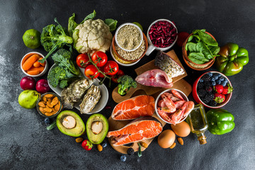 Pescetarian diet plan ingredients, healthy balanced grocery food, fresh fruit, berries, fish and shellfish clams,  black background copy space  Wall mural