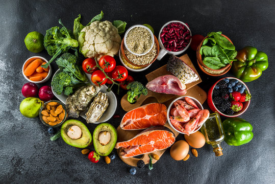 Pescetarian diet plan ingredients, healthy balanced grocery food, fresh fruit, berries, fish and shellfish clams,  black background copy space