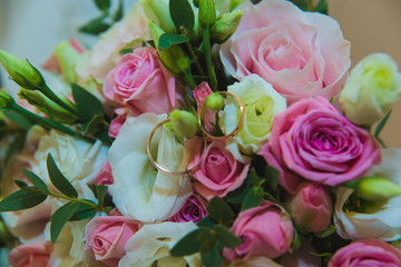 Beautiful delicate wedding bouquet of white and pink roses and wedding rings of the bride and groom.