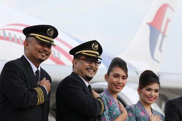 Malaysia Airlines crew members pose for a photograph in front of a plane at Kuala Lumpur International Airport in Sepang