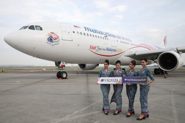 "Malaysia Airlines crew members holding ""Visit Malaysia 2020"" sign pose for a photograph in front of a n Airbus A330 plane at Kuala Lumpur International Airport in Sepang"