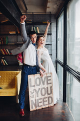 Portrait of lovely newlywed couple holding wooden signboard with message all you need is love. Husband kissing his wife in bookshop.