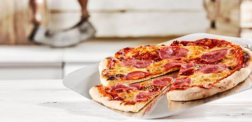 Cadres-photo bureau Pizzeria Freshly prepared Italian salami pizza on a paddle