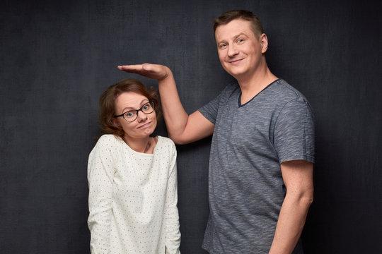 Shot of funny tall man and short woman