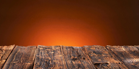 Fotobehang Pizzeria Old rustic wooden table top with warm orange glow