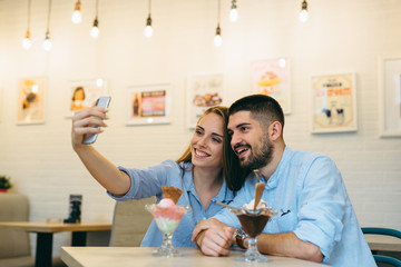 happy couple eating ice cream and using cellphone indoor