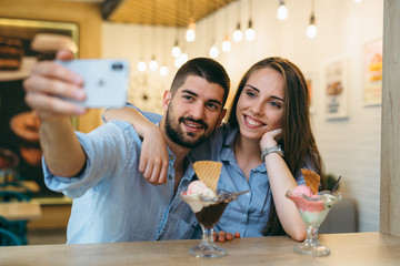 happy couple taking picture while eating ice cream indoor
