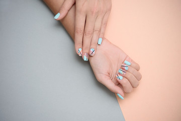 Foto op Canvas Manicure Beautiful female manicure on a pastel color background.