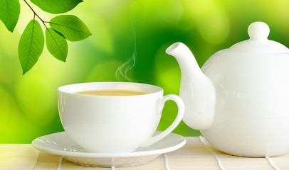 Cup of green tea and white ceramic teapot on wooden table.