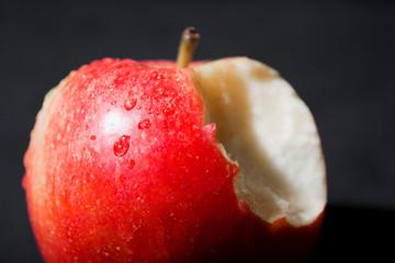 Manzana roja mordida con gotas de agua sobre fondo negro.