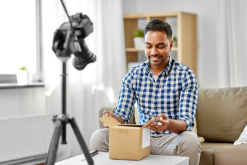 mail delivery, shipment and blogging concept - happy indian male blogger opening parcel box and recording unboxing video with camera at home