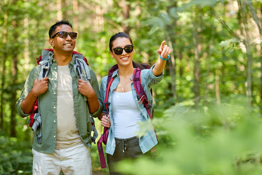 travel, tourism, hike and people concept - mixed race couple with backpacks in forest