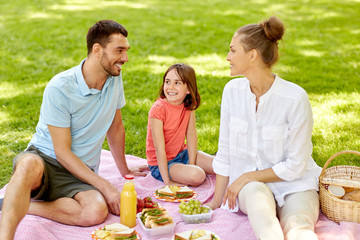 family, leisure and people concept - happy mother, father and daughter having picnic at summer park