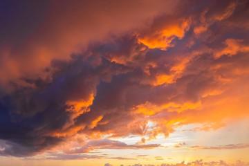 Fototapeten Dunkelbraun Dramatic sunset through a cloudy dark sky over the ocean.
