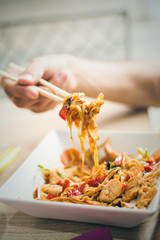 man hand with chopsticks eat thai food closeup selective focus