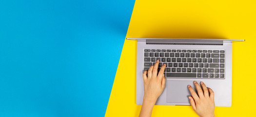 Kid hands typing on laptop computer keyboard, top view, yellow and blue background