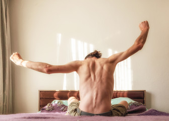 Back view of a Caucasian, naked man waking up in bed and stretching his arms with copy space
